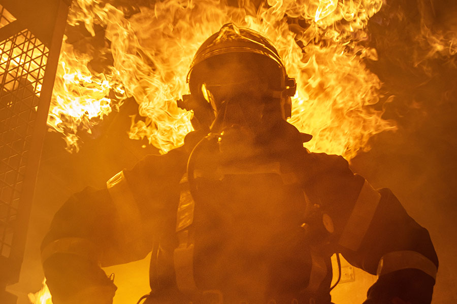 Firefighter standing in front of inferno